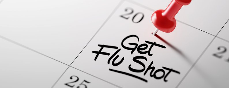 'Get Flu Shot' written on a calendar with red push pin