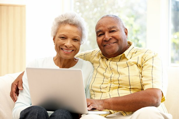 Senior couple on the couch using a laptop