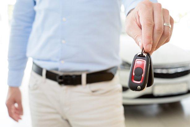 Close-up of man giving away car keys