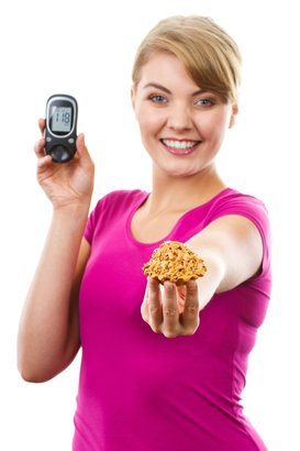 happy woman holding glucose meter in one hand and cupcake in other