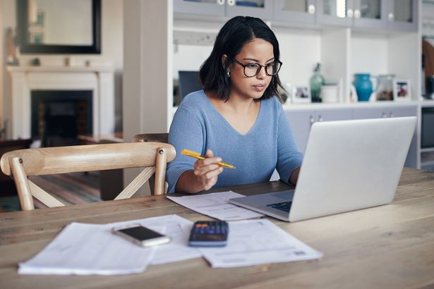 woman at home looking at laptop with papers and calculator on desk