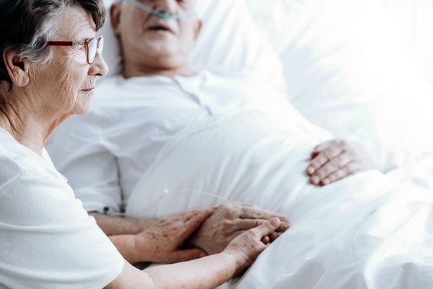 elderly woman holding husband's hand in hospital bed