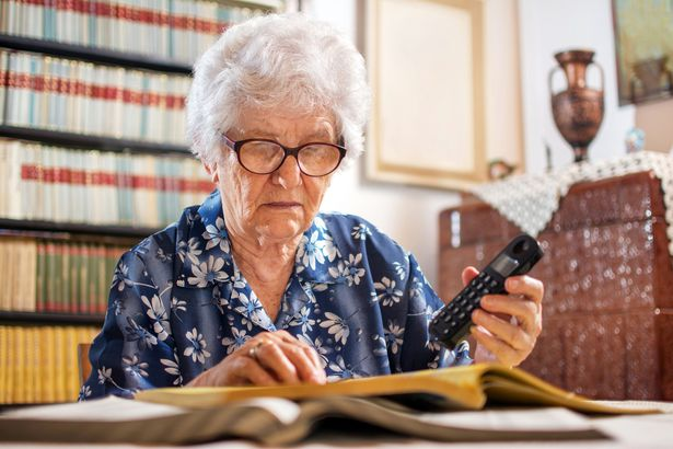 elderly woman looking through phonebook with phone in hand