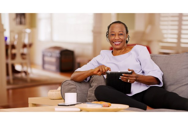 Elderly woman sitting on her couch at home using her tablet