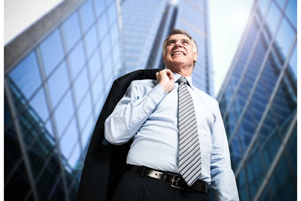 Confident mature businessman in front of tall downtown buildings
