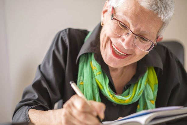 Senior woman smiling and writing in a journal