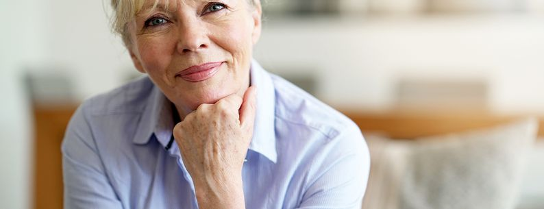 Senior woman sitting on couch at home looking pensive at the camera