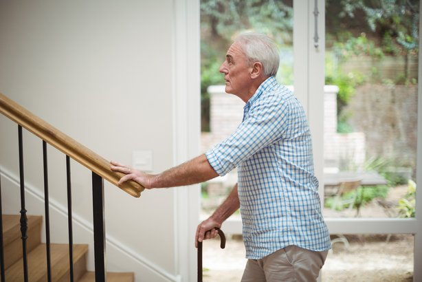 Senior man trying to climb up stairs at home