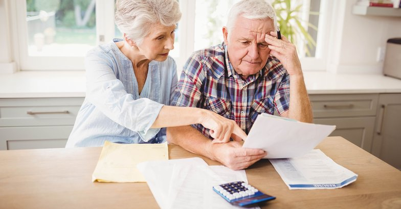 Worried senior couple checking bills
