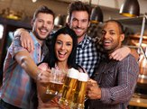 happy young friends drinking beer at pub, laughing, clinking glasses