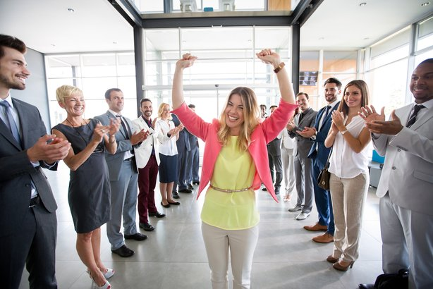 Group of employees congratulating a happy female leader