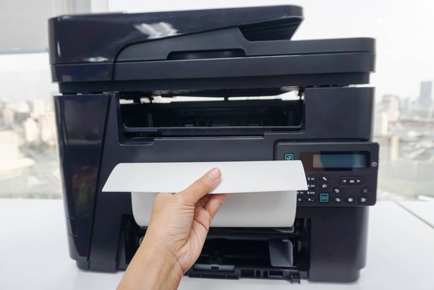 woman officer pull printed business documents from multi functional office printer