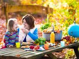 mother and daughter eating picnic outside in autumn