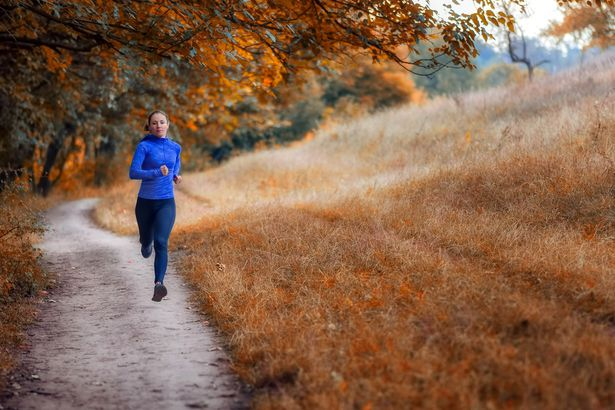woman running between fall field and forest