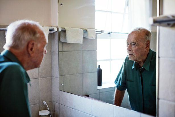 elderly man looking at himself in the mirror