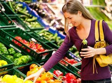 woman in a supermarket at the vegetable shelf shopping for groceries