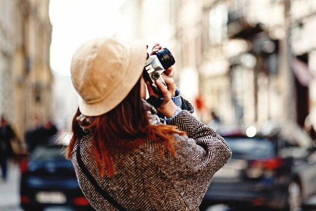 woman taking photo with camera of building