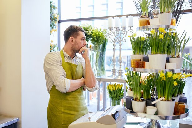 sad florist man with cashbox standing at flower shop counter