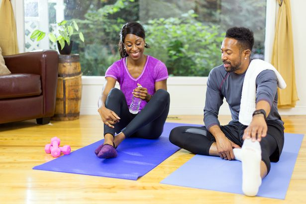 couple stretching getting ready for exercise at home with small weights and yoga mat