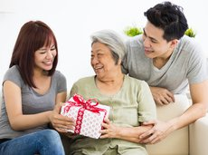 Young Asian couple handing a Christmas gift to a senior woman