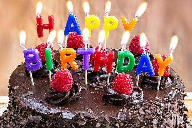 'Happy Birthday' candles on chocolate cake