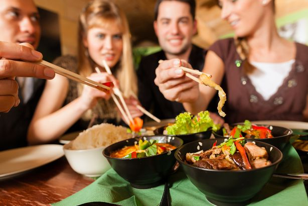 young people eating assorted dishes at Chinese restaurant