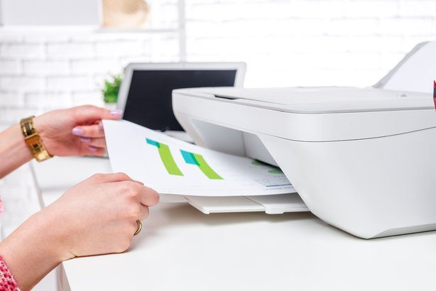 woman hands' getting paper newly printed from printer