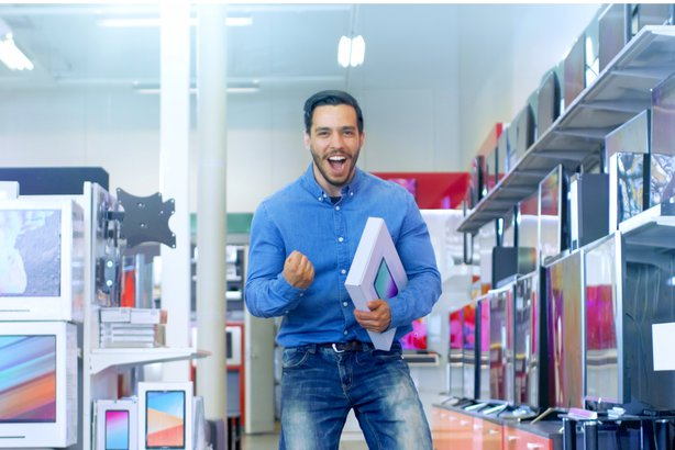 Man in store holding a tablet and is very happy