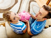back view of couple sitting on sofa with piggy bank