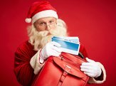 santa with airline tickets and red leather briefcase looking at camera