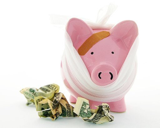 bandaged piggy bank with cash