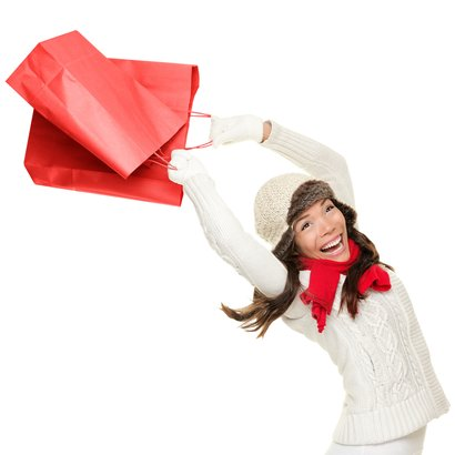 woman holding red shopping bags happy, ecstatic and cheering with energy