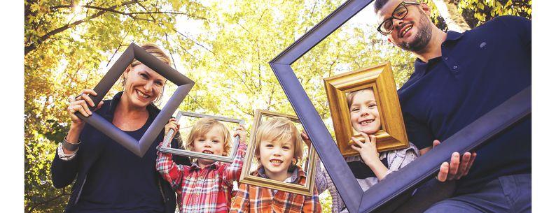 Family portrait posing in an autumn park holding frames