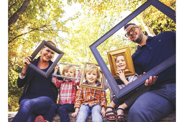Family portrait posing in an autumn park holding frames