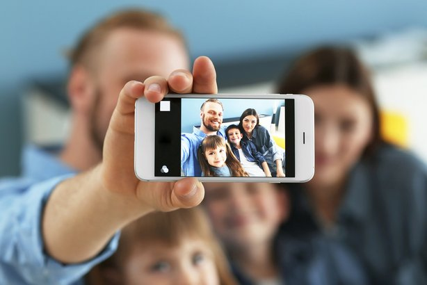 Happy family taking selfie with phone in foreground