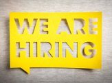 """We are hiring"" yellow banner on white texture background"