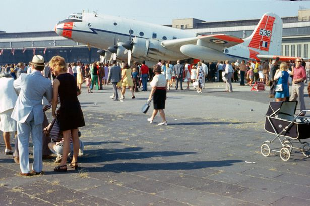 1970s airplane outside airport with people standing around it