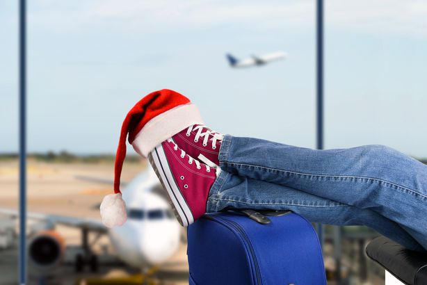 close-up of feet at airport gate sitting on suitcase with santa hat hanging from one shoe, with airplane in the background