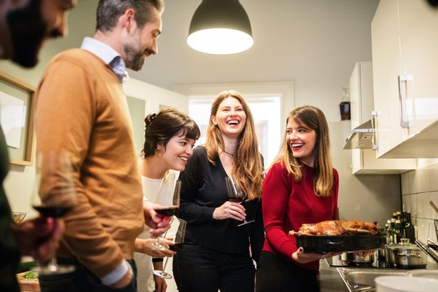 friends laughing and smiling in kitchen with holiday turkey