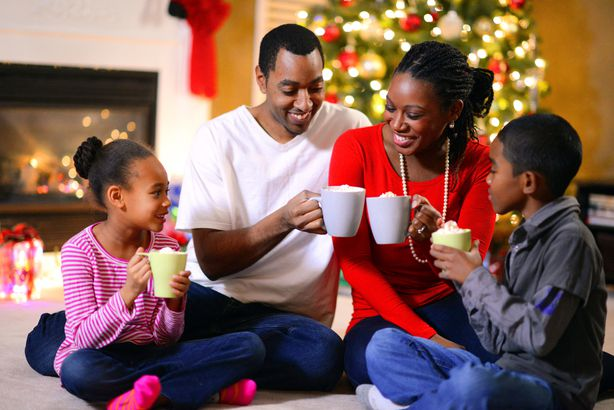 family sitting by christmas fireplace sharing hot chocolate with tree in background