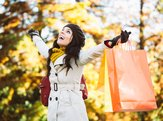 blissful woman holding shopping bags and having fun buying in autumn