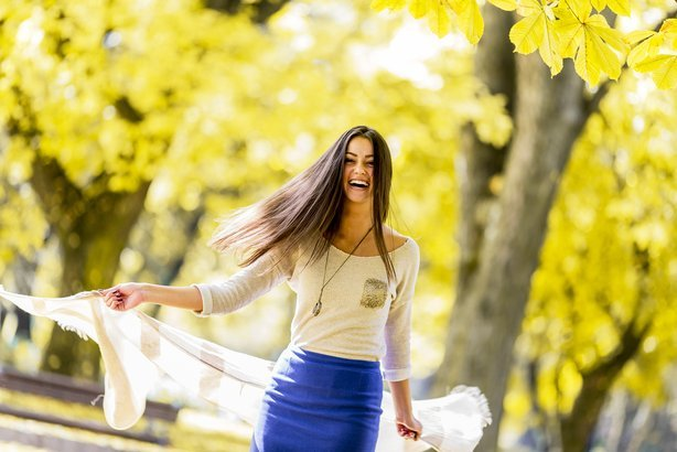 joyful young woman in the autumn forest