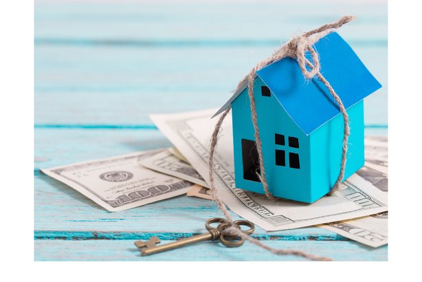 Paper house with key wrapped around it with money on a blue wooden background