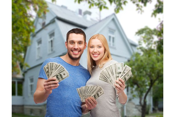 Happy couple holding cash in front of their house