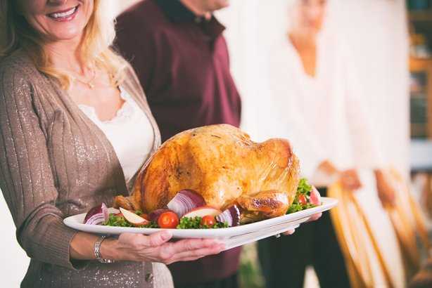 Woman holding platter with roasted turkey for Thanksgiving