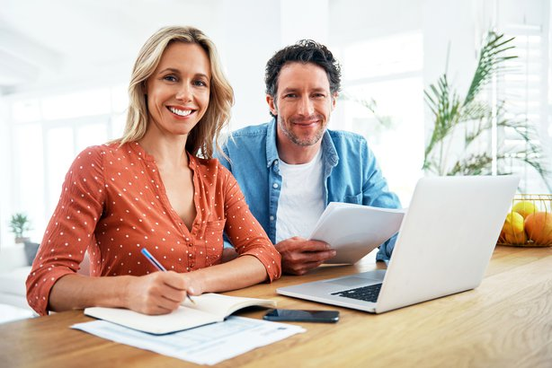 Couple paying bills at home and smiling at camera