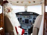 portrait of Santa sitting in cockpit of private jet