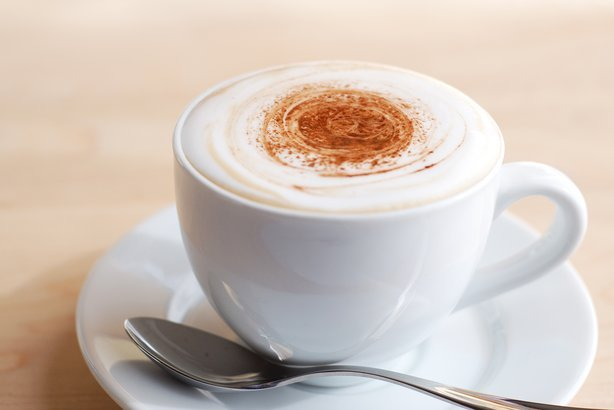 creamy cappuccino in white cup on wooden surface