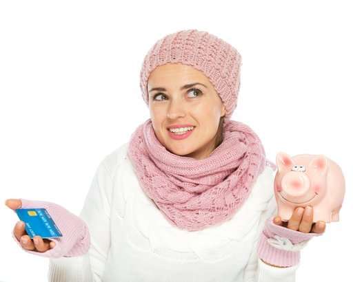 confused woman in knit winter clothing holding credit card and piggy bank