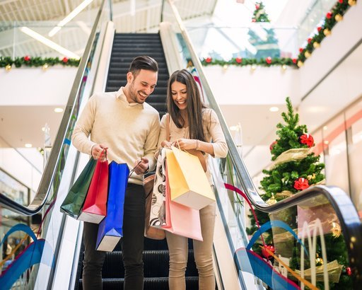 couple with shopping bags in mall at Christmas time